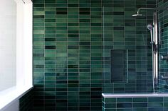 Dark tile, white contrast, steel fixtures.