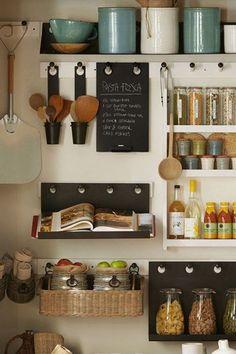 Muro de cocina ordenado con percheras de distintos largos que sirven de soporte para repisas con frascos contenedores de alimentos y especieros, porta cucharas de madera, canastos con frutas, canastos pequeños con paños y servilletas de tela.