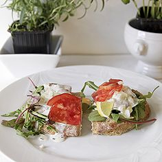 This is a Danish sandwich with herring, tomatoe and chopped onions on top of a bead of rocket salad on a rustic bread.