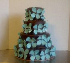 This cake was featured in Arizona Bride Magazine 2006, as breaking the wedding white traditional cakes. The 4 tiers are covered in Chocolate rolled buttercream, think of it as a giant tootsie roll covering the cake! The teal blue accent flowers are made of sugar paste. A perfect cake for a perfect wedding!