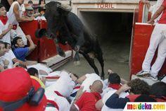 "Seekor banteng melompati tumpukan pelari pada perayaan ""vaquillas"" di Plaza de Toros di festival San Fermin, Pamplona, Spanyol."