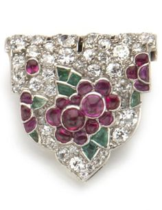 An Art Deco tutti frutti diamond and gem-set clip brooch, French, Cartier, circa 1925. In the form of a shield, pavé-set with old European-cut diamonds and accented with cabochon ruby and emerald flower detail; signed Cartier, Paris; with French assay marks; mounted in platinum and eighteen karat white gold. #Cartier #ArtDeco #clip