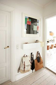 Maximize storage & organization in your entryway by using knobs to hang purses & bags, as well as, an up-cycled flower box to hold keys, scarves, & other random knick-knacks.