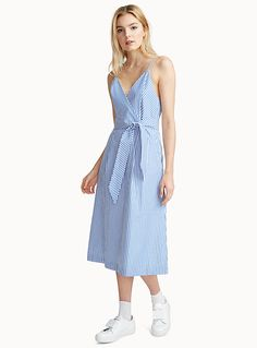 Exclusively from Icône     Gear up for summer in blue-and-white twin stripes with vacation-ready retro charm   Crisp, lightweight 100% cotton poplin with crepe lining   Ultra feminine fit-and-flare style with a crossover bodice and a soft belt that ties in front for a defined waist   Adjustable thin straps   Zip at the back    The model is wearing size small    Length: 102cm, from the top of the bust