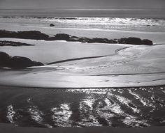 1946 Refugio Beach, California [dark wet rippled sand in foreground, paler sand and rows of dark rocks beyond, sunlight catching edge of surf, high ocean horizon] by Ansel Adams 76.577.3