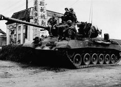 """U.S. troops sit atop a death-dealing medium tank on Sept. 14, 1950, in Gyeongju at a defense position in the Korean War. On the tall pole in background is a tax notice reading """"Tax Day house-to-house tax, July 1-20."""" A Korean policeman, left, directs traffic. Left to right on gun mount are: Bruce Elliott, Steelton, Pa.; Pfc. Robert Ward, Georgiana, Ala.; and Pfc. Paul Zamana, Steubenville, Ohio. On fender is Cpl. Clark Rake of St. Augustine, Fla. (AP Photo)"""
