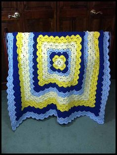 """Beautiful Shells"" blanket #1 done in worsted weight yarn in Soft Yellow, Bright Yellow, Light Blue, and Royal. Measures 46"" square. $110 at http://www.ritamiller.com/afghans/ar216-01.html."