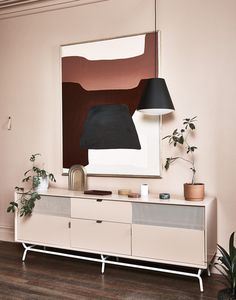Monochromatic office with a styled vignette with a dusty pink dresser, plants, a low-hanging black pendant light and modern art with a pop of red