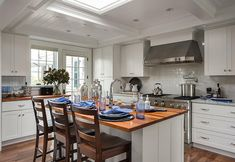 """Kitchen Island. A large skylight was added above the island instead of pendants. This small kitchen is all about the detailing and the trim.  Cabinets Paint Color is """"Sherwin-Williams Pure White"""" _ a great white for crisp white kitchens. #KitchenIsland"""