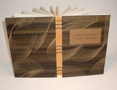 Paste paper over boards, Elephant Hide inside covers and endpapers (tipped in); Coptic binding over gold painted signature spines using black linen thread; title foil-stamped on gold card stock and glued onto recessed cover board.