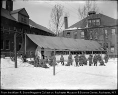 The boys and girls who attend the Edward Mott Moore Open Air School play in the snow on the School 14 Playground in Rochester NY. They are dressed in heavy winter outfits made of matching blanket cloth. One stands on skis