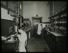 Two staff at work in a chemical laboratory with man in foreground using microscope, STC Woolwich, n.d.. IET Archives NAEST 211/02/42/02/04 (slide 12)