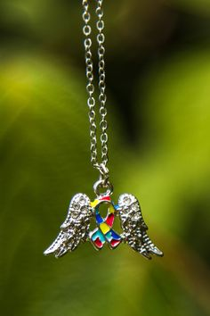 Awareness for loved ones on the autism spectrum is carried by angel wings on our dazzling pendant. The autism puzzle ribbon sits reverently between two angel wings, studded with rhinestones.