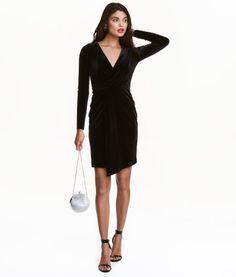 Zwart. Een jurk van velours met lange mouwen, een V-hals en een vastgestikte overslag voor. De jurk heeft elastiek in de taille. Gevoerd met tricot.