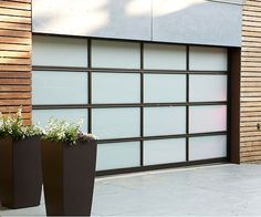 Void of elaborate ornamentation and unnecessary detail, contemporary architecture accentuates simple forms and geometric lines. A striking blend of aluminum and glass gives this garage door a sleek, modern look. Door shown: Clopay Avante Collection www.clopaydoor.com.
