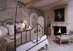 Wow, I could surely have a peaceful nights sleep in this gorgeous room. Love the fireplace, exposed beams, the lovely stone wall,& the beautiful arched door, not to mention the peaceful muted colors.