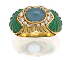 CHALCEDONY, DIAMOND AND CHRYSOPRASE RING, CARTIER, CIRCA 1990 Cenetring a blue chalcedony cabochon above a brilliant-cut diamond surround between carved chrysoprase shoulders, mounted in 18 carat gold, signed Cartier.