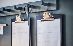 IKEA VÄLBEKANT clipboards hang from hooks on the wall, displaying a work schedule.
