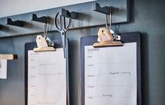 Pranchetas VÄLBEKANT da IKEA penduradas com ganchos na parede, com uma agenda de trabalho