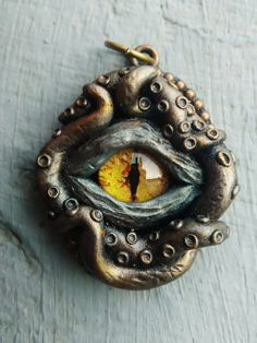 Creepy eye with tentacles pendant. Fully handmade of polymer clay, with hand painted glass eye, all on metal base. Inspired by horror, sci fi and fantasy movies and literature. Perfect gift for those who like gothic jewelry, mythic creatures and dark stories. Light and easy to wear, and looks great and spooky at the same time. #MelianArt #HandmadeJewelry #CthulhuEye #Tentacles #TentacleJewelry #TentacleEyeAmulet #CthulhuTalisman #DeepSeaJewelry #HalloweenJewelry #CreepyNecklace