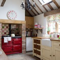 Loving the red stove and that gorgeous apron sink- the curtains, the clock . . .