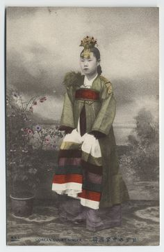 Collection: Willard Dickerman Straight and Early U.S.-Korea Diplomatic Relations, Cornell University Library  Title: A Corean court singer  Date: ca. 1904  Place: Asia: South Korea  Type: Postcards/Ephemera  Description: Courtesans frequently danced and sang during festivities at the royal court. This singer/dancer is shown wearing a 'hwagwan' (a small crown decorated with flowers and jewels), and a long, well-tailored silk jacket over a skirt. Her hands grasp colorful pieces of cloth which…