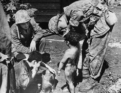 American marines wash children they have rescued from a dugout, ca. 1945. Northern Mariana Islands