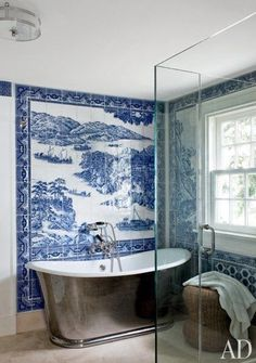 Blue and White Chinoiserie-inspired tiled bathroom with gleaming stainless steel freestanding bathtub by Russel Piccione.
