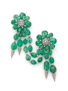 FULCO DI VERDURA 1958 Front bodice transformations in platinum, 18K white gold with emeralds and pebbles, composed of two pin-shaped clips flowers, petals and pistils underlined diamonds; each holding a tassel double-ended with a crimped diamond lanyard; linked by a double chain adorned with diamonds emeralds chanted. Clips can be worn individually, the pendants and the link are detachable. Signed pin clips.