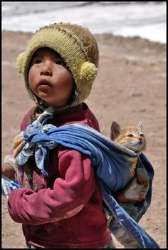 "Little Girl from Peru: ""Sorry, what did you say? Yes! Of course! I ALWAYS carry my kitten this way! What a silly question!"""