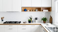 I like the timber touches in white cabinetry, including small open shelving, and the diamond-shaped backsplash tiles. By Cantilever Interiors