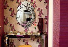 Parede com fundo rosa e estampa floral abriga o espelho com moldura prateada. Apenas uma das paredes da sala ganhou a decoração com esse tipo de papel  Casa e Jardim / Casa e Jardim