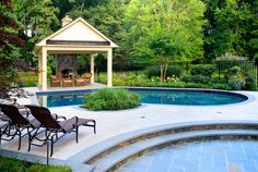 A poolside deck with lounge areas, as well as seating areas, with an outdoor fireplace as the focal point.