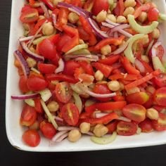 Greek Salad: A fresh and delicious salad with tomatoes, cucumber, red onion, red bell pepper, and garbanzo beans tossed in a lemon and oreg...FEEL FREE to serve on a bed of lettuce and add kalamata or black olives if you desire.