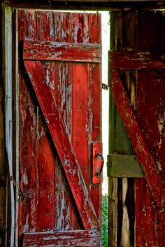Just a peek outside through a red #barn #door... it looks like this door has taken a toll from its wear and tear daily use.