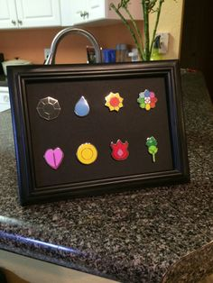 Pokemon badges in a frame. They were pins he bought at megacon. I thought they would be an awesome decor piece in the house.