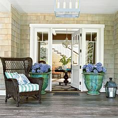 This wide front porch boasts a welcoming entryway. Wicker furniture and Hamptons-style shingles give the front door classic style. Style At Home, Home Staging, Outdoor Rooms, Outdoor Living, Outdoor Decor, Sweet Home, Lanterns Decor, Coastal Living, Coastal Entryway