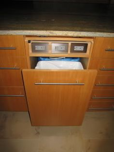 "We also have space for a small drawer above our trash pullouts. One we use for wine openers, stoppers, etc. The other we ""sacrificed"" to provide electrical outlets to that side of the island. The drawer ""front"" flips up for the outlets or down to cover them."