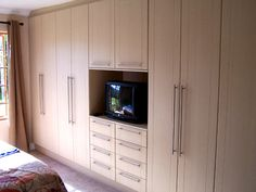 BEDROOM CUPBOARDS WITH ROYAL BIRCH SHAKER WRAP DOORS, STAINLESS STEEL BAR HANDLES, 8 DRAWERS ON HEAVYDUTY BALL BEARING RUNNERS AND DRESSER PLACE FOR TV