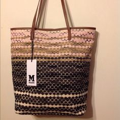 M Missoni Crochet Knit Leather Trim Handbag Tote Dust bag not included. Handbag is made of  crochet knit fabric with brown leather trim. The fabric is a multi-colored. The inside of this bag is lined striped in cotton fabric and features a zippered pocket with the rest of the bag being open. The handbag is very light weight knit, does not weigh much w/out anything inside. A magnet closes the handbag. Defect: I bought this handbag at a department store and didn't realize the stitching on the…