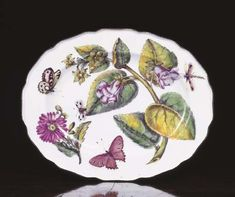 A Chelsea 'Hans Sloane' oval dish  Circa 1755  Painted with a puce flowered plant, a chrysanthemum, a dragonfly and an insect within a shaped brown-line rim (very slight wear to pink flower and chrysanthemum)  11 3/8 in. (28.8 cm.) wide