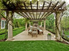 A vine-covered pergola adds a touch of magic to this outside dining area.