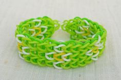 Rainbow Loom bracelet made from rubber bands, neon green, white, yellow and green in the background