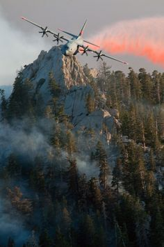 A C-130J Super Hercules crew assigned to the 146th Airlift Wing, the California Air National Guard unit at Channel Islands ANGS, releases fire retardant over the trees in the mountains above Palm Springs, California, on 19 July 2013. The 146th AW, one of three ANG and one Air Force Reserve Command units equipped with the Modular Airborne Firefighting System, or MAFFS, was activated to assist commercial air tankers in in fighting wildfires.