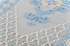 Tappeto realizzato manualmente con la tecnica pibiones punto semipieno caratterizzato dal motivo giglio reale. Colore ecru e azzurro. Misure: 160 X 61 cm. Tratt