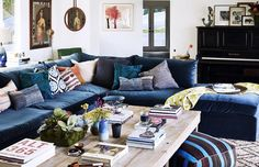 Rachel Bilson and Hayden Christensen's living room, featuring a blue velvet sofa, distressed coffee table and hung artwork.