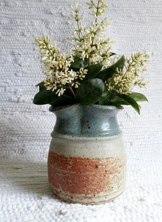 Vintage handmade stoneware vase. Shino glaze with brown speckles with shades of   light gray  rusty orange  dusty sage green dominates the piece  $22