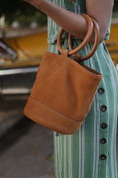 Desi is wearing: Hermès Oran sandals, Simon Biller Bucket Bag Bonsai, Green striped linen dress, Céline Tilda Sunglasses - teetharejade.com
