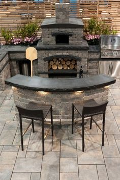 Outdoor kitchen in stone. I like the lights under the bar.
