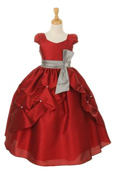 Sure to be a hit this season, this Dupioni silk dress will have your little one feel like the belle of the ball! The full skirt has a top layer of delicate pickups adorned with rhinestone accents. We absolutely love the cap puff sleeves and the very subtle sweetheart neckline. Dress comes with an attached sash that has the cutest rhinestone flower pendant. The dress is great because it is SUPER cute for a wedding, but can be reused after it is over and it will photograph great at any…